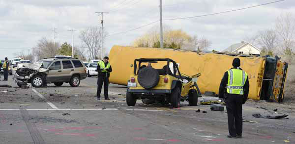 Investigators gather evidence from the scene of a three vehicle accident, including a school bus where the driver of a Jeep Wrangler was killed on Friday, April 5, 2013, near Wadsworth, Ill.  Over two dozen school children were on the bus, most receiving minor injuries. &#40;AP Photo&#47;Jim Prisching&#41; <span class=meta>(Photo&#47;Jim Prisching)</span>