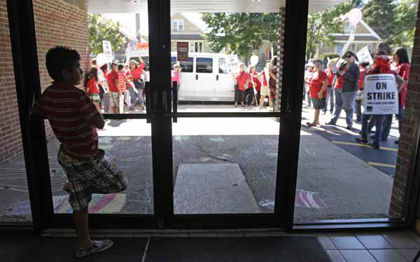 Student Edgar Guerra, 10, watches Chicago Public School teachers picket outside Maranatha Church in Chicago where Mayor Rahm Emanuel was visiting students that were taking part at the Safe Haven program Monday, Sept. 10, 2012. The church was providing students with structured activities and a safe environment during the teachers strike. Thousands of teachers walked off the job Monday in the nation&#39;s third-largest school district for the first time in 25 years after union leaders announced they were far from resolving a contract dispute with school district officials. &#40;AP Photo&#47;M. Spencer Green&#41; <span class=meta>(AP Photo&#47; M. Spencer Green)</span>