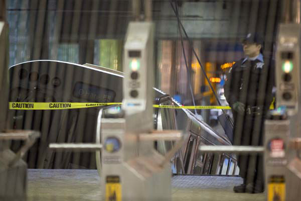 A police officer stands near a Chicago Transit Authority train car that derailed at the O'Hare Airport station early Monday, March 24, 2014, in Chicago. More than 30 people were injured after the eight-car train plowed across a platform and scaled an escalator at the underground station. (AP Photo/Andrew A. Nelles)