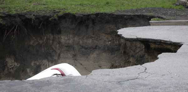 A section of a car can be seen in a gaping sinkhole that opened up a residential street on Chicago&#39;s South Side after a cast iron water main dating back to 1915 broke during a massive rain storm Thursday, April 18, 2013, in Chicago. The hole spanned the entire width of the road and chewed up grassy areas abutting the sidewalk. Two of the cars that disappeared inside had been parked, but a third was being driven when the road buckled and caved in. Only the hood of one of the vehicles could be seen peeking from the chasm.&#40;AP Photo&#47;M. Spencer Green&#41; <span class=meta>(AP Photo&#47; M. Spencer Green)</span>