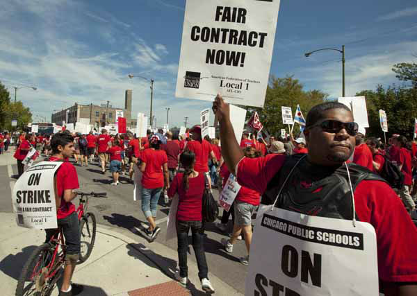 A large group of public school teachers seek support from neighborhood communities as they march on streets surrounding John Marshall Metropolitan High School on Wednesday, Sept. 12, 2012 in West Chicago. Teachers walked off the job Monday for the first time in 25 years over issues that include pay raises, classroom conditions, job security and teacher evaluations. &#40;AP Photo&#47;Sitthixay Ditthavong&#41; <span class=meta>(AP Photo&#47; Sitthixay Ditthavong)</span>