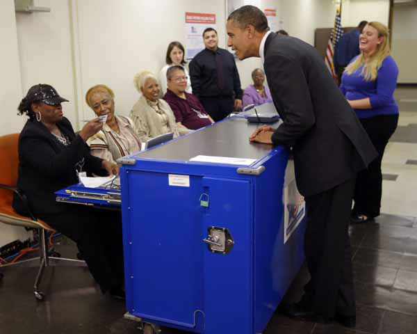 Election official Marie Holmes, left, looks over President Barack Obama&#39;s drivers license so he can cast his vote during early voting in the 2012 election at the Martin Luther King Community Center, Thursday, Oct. 25, 2012, in Chicago. &#40;AP Photo&#47;Pablo Martinez Monsivais&#41; <span class=meta>(AP Photo&#47; Pablo Martinez Monsivais)</span>