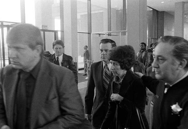 Mrs. Harry Piest is assisted by a deputy, right, as she leaves the Cook County Criminal Court in Chicago on Wednesday, Jan. 10, 1979 following a hearing for accused mass murder suspect John Wayne Gacy, Jr. Gacy has been charged with murder in connection with the death of her son, Robert, whose body has not been found. Gacy?s lawyer entered a plea of innocent to each of seven murder charges. (AP Photo/CEK)