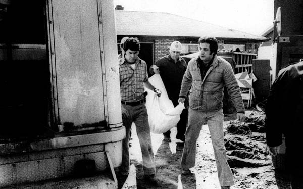 Cook County sheriff's police remove the remains of another body found Friday March 17, 1979 at the Chicago suburban home of accused murderer John Wayne Gacy. The body, found under an addition to the Gacy home, is the 29th to be found beneath the home or buried elsewhere on the property. (AP PHOTO)