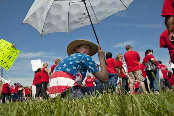 "<div class=""meta ""><span class=""caption-text "">Elementary drama teacher Mary O'Malley shades herself with an umbrella before joining a large group of public school teachers rallying at John Marshall Metropolitan High School on Wednesday, Sept. 12, 2012 in West Chicago. Teachers walked off the job Monday for the first time in 25 years over issues that include pay raises, classroom conditions, job security and teacher evaluations. (AP Photo/Sitthixay Ditthavong) (AP Photo/ Sitthixay Ditthavong)</span></div>"