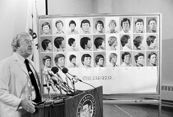 Cook County Medical Examiner, Dr. Robert J. Stein, speaks to members of the press on Monday, July 14, 1980 in Chicago asking for help in identifying the remaining bodies found in the crawlspace of John Wayne Gacy?s home. The picture composite behind Stain is of faces reconstructed from unidentified skuls, found in the crawlspace. (AP Photo/FHJ)