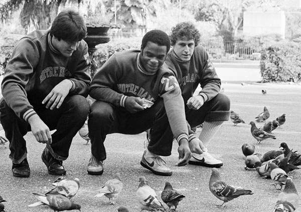 Three members of Notre Dames football squad have a time out between team meetings and practice to get in a little time feeding the pigeons in Jackson Square, Saturday, Dec. 27, 1980, New Orleans, La. Members of the Fighting Irish, from left are: offensive tackle Phil Pozderac of Garfield Heights, Ohio; cornerback Dave Duerson of Muncie, Ind.; and linebacker Joe Rudzinski of Farmington, Minn. Notre Dame takes on Georgia in the Sugar Bowl Jan. 1. (AP Photo)