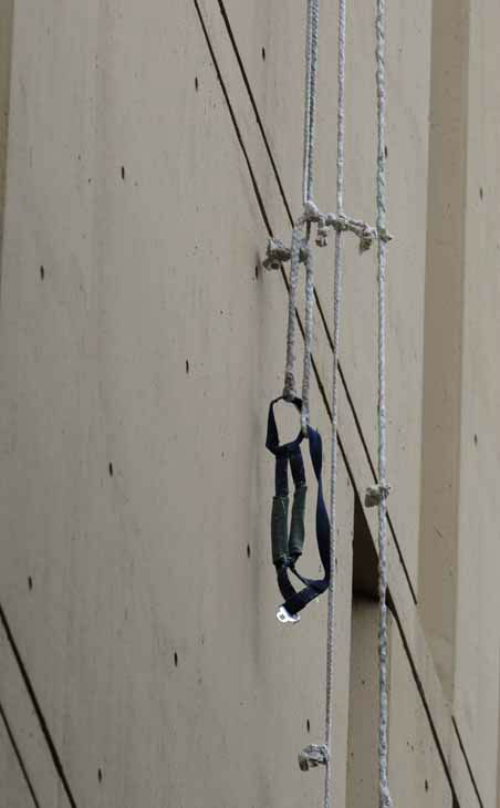 A harness and the end of a rope dangles from a window on the back side of the Metropolitan Correctional Center Tuesday, Dec. 18, 2012, in Chicago. Two convicted bank robbers used a knotted rope or bed sheets to escape from the federal prison window high above downtown Chicago early Tuesday, a week after one of them made a courtroom vow of retribution, to federal judge. The escape occurred sometime between 5 a.m. and 8:45 a.m. when the inmates were discovered missing, Chicago Police Sgt. Mark Lazarro said. Hours later, what appeared to be a rope, knotted at six-foot intervals, could be seen dangling into an alley from a window of the Metropolitan Correctional Center approximately 20 stories above the ground. &#40;AP Photo&#47;M. Spencer Green&#41; <span class=meta>(AP Photo&#47; M. Spencer Green)</span>