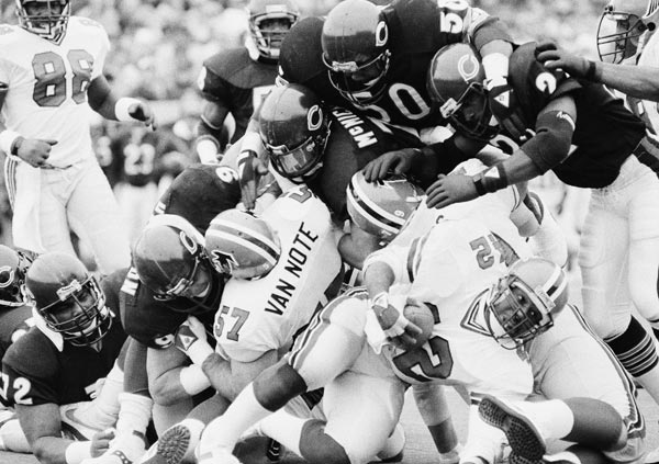 Atlanta Falcons Gerald Riggs (42) gets a dose of heavy coverage by Chicago Bears defenders Mike Singletary (50), Dave Duerson (22), and Steve McMichaels, during first half NFL action on Sunday, Nov. 24, 1985 in Chicago. (AP Photo/Charlie Bennett)