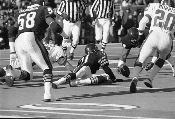 Bears' Dave Duerson (22) in center, and Leslie Frazier (21), dive for a loose ball during first period action at Soldier Field in Chicago, Sunday, Jan. 5, 1986. Giants Joe Morris (20) is at right. (AP Photo/Fred Jewell)