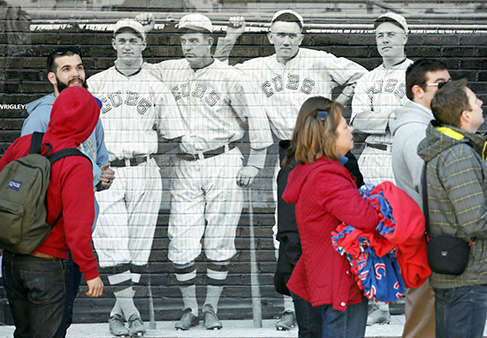 Baseball fans walk past a mural of four 1918 Chicago Cubs&#39; players as they enter Wrigley Field on the 100th anniversary of the first baseball game at the park, before a game between the Arizona Diamondbacks and Chicago Cubs, Wednesday, April 23, 2014, in Chicago. &#40;AP Photo&#47;Charles Rex Arbogast&#41; <span class=meta>(Photo&#47;Charles Rex Arbogast)</span>
