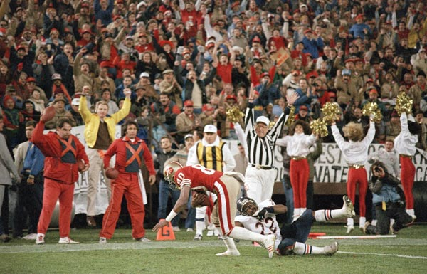 San Francisco 49ers wide receiver Jerry Rice (80) takes a short pass across the end zone with Chicago Bears safety Dave Duerson (22) in tow for a touchdown in the first quarter of game on Monday, Dec. 14, 1987 in San Francisco. (AP Photo/Paul Sakuma)