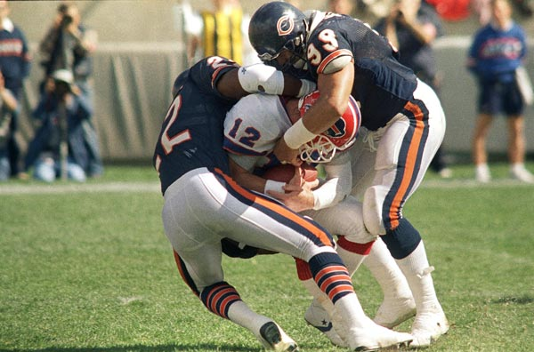 Buffalo Bills quarterback Jim Kelly is sacked by Chicago Bears Dave Duerson (22) and Dan Hampton (99) for a 9-yard loss in the second quarter in Chicago, Sunday, Oct. 2, 1988. (AP Photo/Mark Elias)