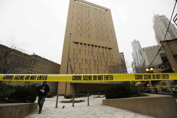 Police tape surrounds the Metropolitan Correctional Center Tuesday, Dec. 18, 2012, in Chicago. Two convicted bank robbers used a knotted rope or bed sheets to escape from the federal prison window high above downtown Chicago early Tuesday, a week after one of them made a courtroom vow of retribution, to federal judge. The escape occurred sometime between 5 a.m. and 8:45 a.m. when the inmates were discovered missing, Chicago Police Sgt. Mark Lazarro said. Hours later, what appeared to be a rope, knotted at six-foot intervals, could be seen dangling into an alley from a window of the Metropolitan Correctional Center approximately 20 stories above the ground. &#40;AP Photo&#47;M. Spencer Green&#41; <span class=meta>(AP Photo&#47; M. Spencer Green)</span>