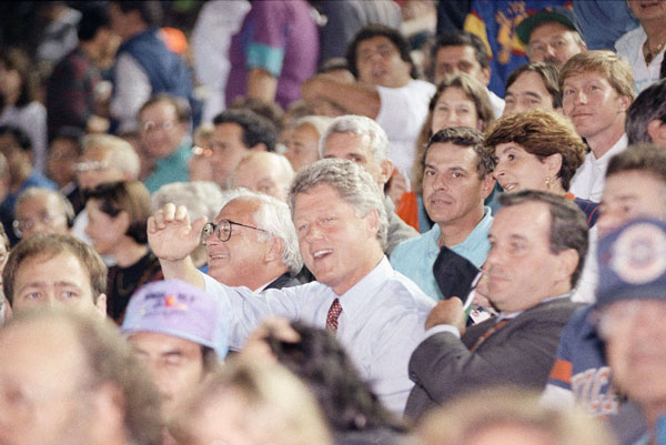 Democratic presidential candidate Bill Clinton waves while attending a game between the Chicago Bears and New York Giants in Chicago, Sept. 22, 1992. Chicago Mayor Richard Daley, right, sits next to the candidate. (AP Photo/Stephan Savoia)