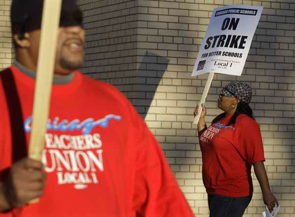 Chicago teachers Michael Williams and Alma Hill walk a picket line outside Benjamin Banneker Elementary School in Chicago, early Monday, Sept. 10, 2012, after the teachers went on strike for the first time in 25 years. Union and district officials failed to reach a contract agreement despite intense weekend negotiations. &#40;AP Photo&#47;M. Spencer Green&#41; <span class=meta>(AP Photo&#47; M. Spencer Green)</span>