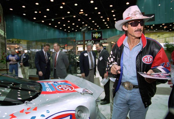 Richard Petty signs autographs during a press conference for the 1996 Pontiac Grand Prix at the Chicago Auto Show.  (AP Photo/Mike Fisher)