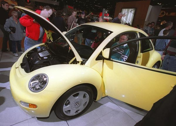 People attending the opening of the 90th edition of the Chicago Auto Show at McCormick Place South inspect the new Volkswagen Beetle Saturday, Feb. 7, 1998. (AP Photo/Peter Barreras)
