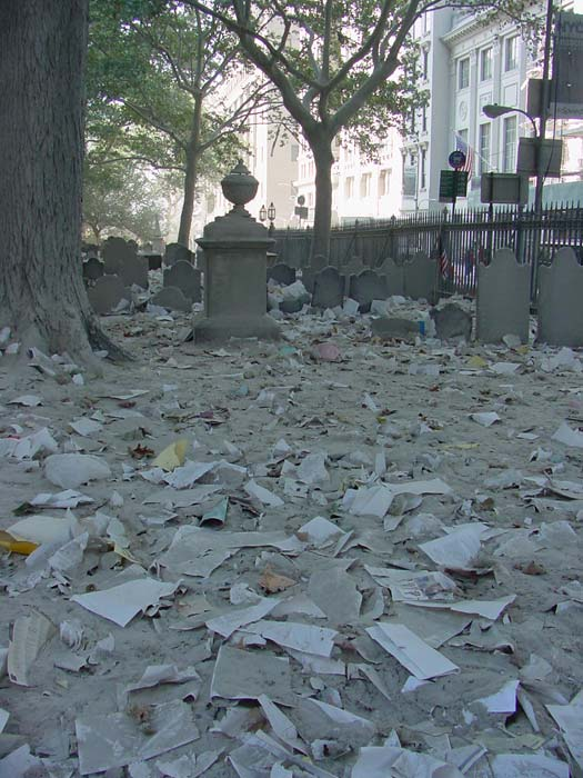 Papers, debris and concrete dust fill a cemetery