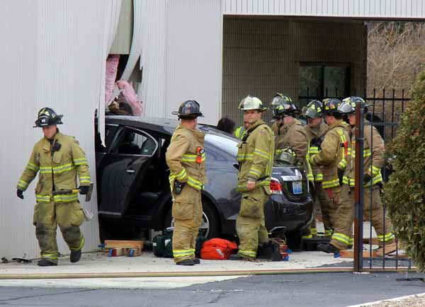 Naperville firefighters respond around 1 p.m. Friday, Nov. 30, 2012, to a vehicle that crashed into the wall of a business at Rosin Eye Car, 705 East Ogden Ave., Naperville, IL.  |  photos by Brian Delaney
