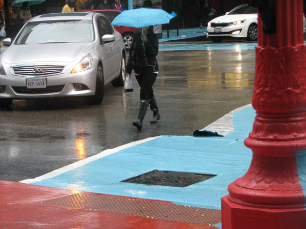 A pedestrian walking across the street, in the rain, passes a torn part of the crosswalk at the Color Jam intersection. Photo taken May 31, 2012&#40;ABC7Chicago.com&#47; Evan Peterson&#41; <span class=meta>(ABC7Chicago.com&#47; Evan Peterson)</span>