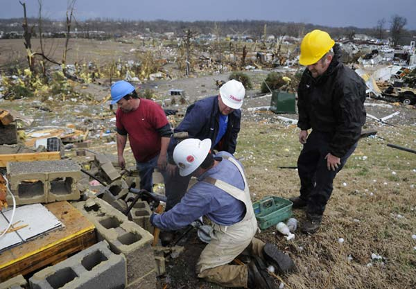 Workers with the Midwest Natural Gas Company seal a gas leak at the remains of a building following severe storms that struck Friday, March 2, 2012, in Henryville, Ind. Tornadoes ripped across several small southern Indiana towns on Friday, killing at least three people and leaving behind miles of flattened devastation along the border with Kentucky. (AP Photo/Timothy D. Easley)