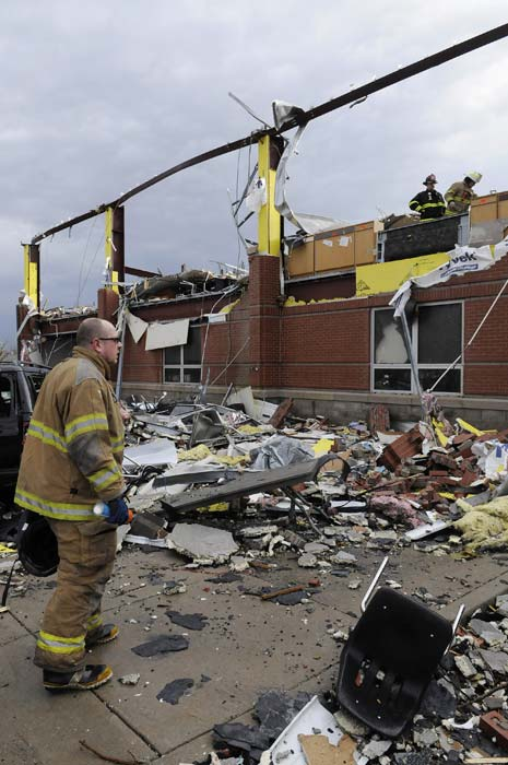 Firefighters with the Jeffersonville, Ind., fire department coordinate a search of the Henryville Middle School following severe storms Friday, March 2, 2012, in Henryville, Ind. Tornadoes ripped across several small southern Indiana towns on Friday, killing at least three people and leaving behind miles of flattened devastation along the border with Kentucky. (AP Photo/Timothy D. Easley)