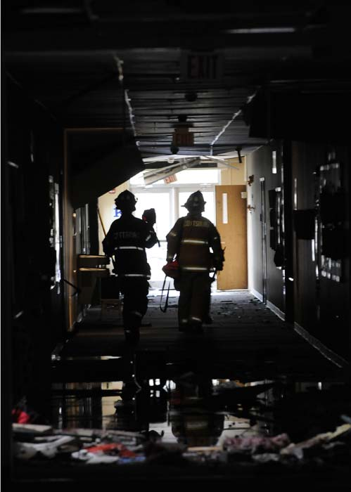 Firefighters with the Jeffersonville Fire Department do a room-by-room search of the Henryville Middle School following severe storms Friday, March 2, 2012, in Henryville, Ind. Tornadoes ripped across several small southern Indiana towns on Friday, killing at least three people and leaving behind miles of flattened devastation along the border with Kentucky. (AP Photo/Timothy D. Easley)