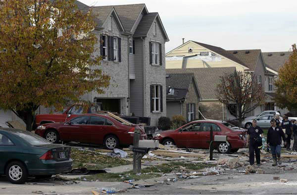 Emergency workers walk down a street across from a home heavily damaged by an explosion  Sunday, Nov. 11, 2012, in Indianapolis. Nearly three dozen homes were damaged or destroyed, and seven people were taken to a hospital with injuries, authorities said Sunday. The powerful nighttime blast shattered windows, crumpled walls and could be felt at least three miles away. &#40;AP Photo&#47;Darron Cummings&#41; <span class=meta>(AP Photo&#47; Darron Cummings)</span>