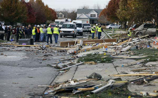 Emergency personnel work at the site of a home that was destroyed by an explosion Sunday, Nov. 11, 2012, in Indianapolis. Nearly three dozen homes were damaged or destroyed, and seven people were taken to a hospital with injuries, authorities said Sunday. The powerful nighttime blast shattered windows, crumpled walls and could be felt at least three miles away. &#40;AP Photo&#47;Darron Cummings&#41; <span class=meta>(AP Photo&#47; Darron Cummings)</span>