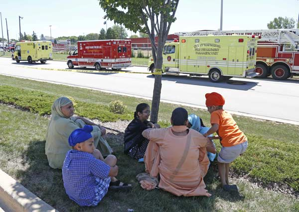 Bystanders sit in the shade at the scene of a shooting inside The Sikh Temple in Oak Creek, Wis, Sunday, Aug 5, 2012. Greenfield Police Chief Bradley Wentlandt says tactical officers have been through the temple where shots were fired about 10:30 a.m. Sunday. He says they found four people inside the building and three people outside. (AP Photo/Jeffrey Phelps)