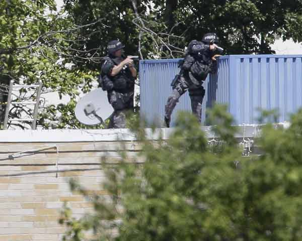 Armed police investigate the Sikh Temple in Oak Creek, Wis. where a shooting took place on Sunday, Aug. 5, 2012. (AP Photo/Jeffrey Phelps)