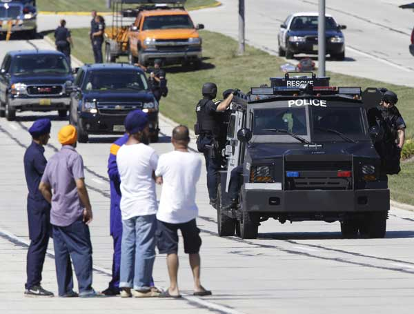 "<div class=""meta ""><span class=""caption-text "">People watch police personnel outside the Sikh Temple in Oak Creek, Wis., where a shooting took place Sunday, Aug 5, 2012. (AP Photo/Jeffrey Phelps)</span></div>"