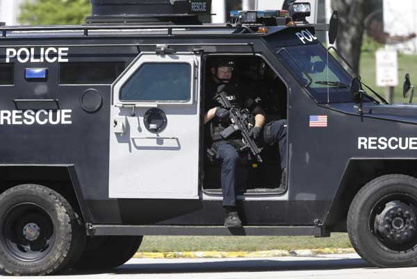 Police personnel move outside the Sikh Temple in Oak Creek, Wis., where a shooting took place Sunday, Aug 5, 2012. (AP Photo/Jeffrey Phelps)