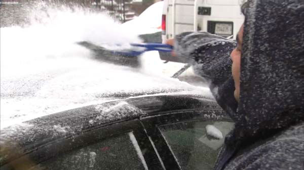 A man brushes snow off of his car. <span class=meta>(ABC 7 Chicago)</span>