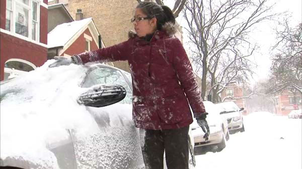 A woman scrapes snow off of her car's windshield.