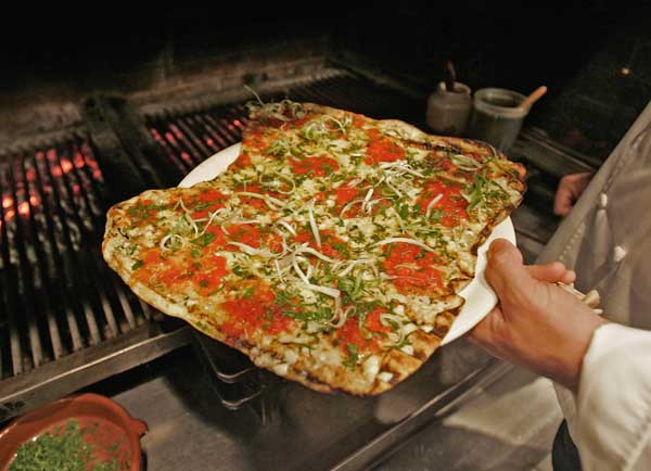 "<div class=""meta ""><span class=""caption-text "">No. 2: Providence, RI's grilled pizza. Only in Providence, RI, can you find pizza made on a grill. The dough is grilled on both side before toppings are added, according to  Travel and Leisure, which ranked Providence pizza second. ( A pizza is pulled off the grill at Al Forno in Providence, R.I. in June 2006. (AP Photo/Richard Drew))</span></div>"