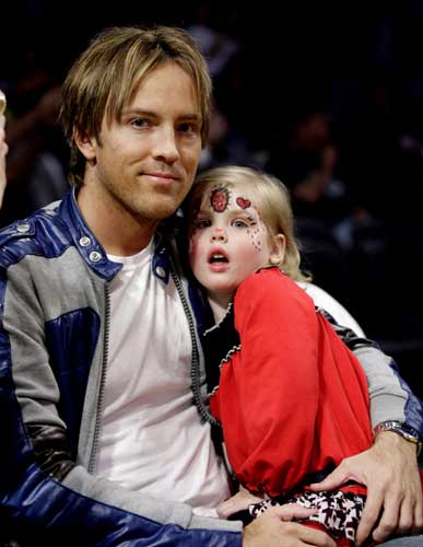 In this Nov. 8, 2008 file photo, Larry Birkhead, left, and his daughter, Dannielynn Birkhead, the daughter of the late Anna Nicole Smith, watch the New Orleans Hornets, Los Angeles Lakers NBA basketball game in Los Angeles. (AP Photo/Francis Specker, file)