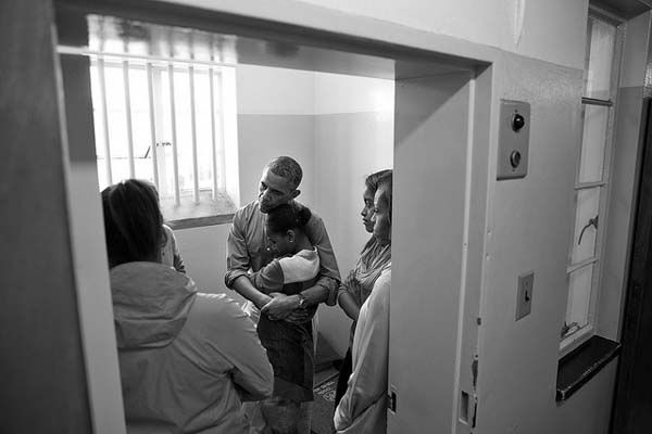 June 30, 2013: A quiet moment inside Nelson Mandela&#39;s former prison cell as the President embraced Sasha while the Obama family was listening to Ahmed Kathrada recount his years spent imprisoned here on Robben Island in Cape Town, South Africa. Nelson Mandela was imprisoned for 27 years, initially in this prison cell. Kathrada was imprisoned at Robben Island for 18 years.   <span class=meta>(Official White House Photo by Pete Souza)</span>