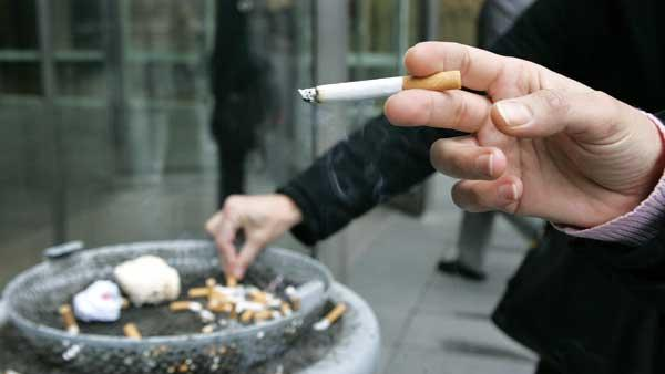 Employees smoke outside the entrance of an office building in the complex in Paris, Wednesday, Jan. 31, 2007.   (AP Photo/Jacques Brinon)