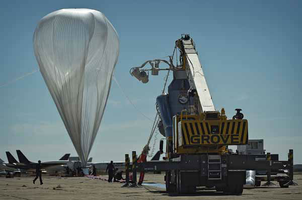 In this photo provided by Red Bull Stratos, the  55-story, ultra-thin helium balloon that was to carry extreme athlete Felix Baumgartner to his 23-mile free fall twists in the wind Tuesday, Oct. 9, 2012 in Roswell, N.M.  A 25 mph gust of wind rushed so fast that it spun the still-inflating balloon as if it was a giant plastic grocery bag, raising concerns at mission control about whether it was damaged from the jostling. The jump will be postponed until at least Thursday. &#40;AP Photo&#47;Red Bull Stratos, Joerg Mitter&#41; <span class=meta>(AP Photo&#47; Joerg Mitter)</span>