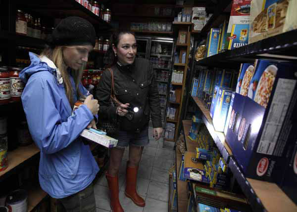 Two women shop for groceries by flashlight in the Tribeca neighborhood of New York, Tuesday, Oct. 30, 2012. ConEd cut power Moday to some neighborhoods served by underground lines as the advancing storm surge from Hurricane Sandy threatened to flood substations. Floodwaters later led to explosions that disabled a substation in Lower Manhattan, cutting power tens of thousands of customers south of 39th Street. &#40;AP Photo&#47;Richard Drew&#41; <span class=meta>(AP Photo&#47; Richard Drew)</span>