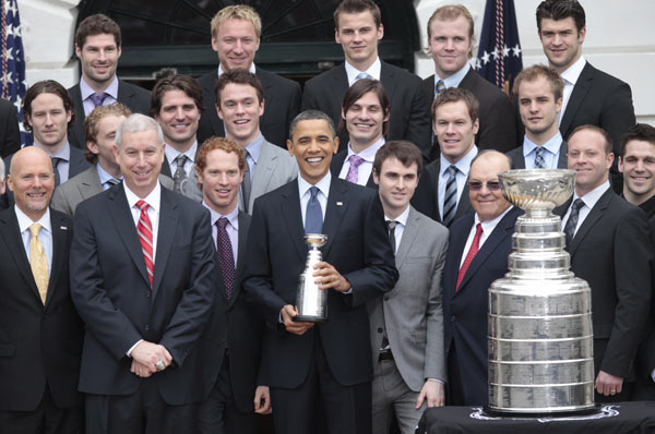 President Barack Obama, center, holds a miniature Stanley Cup trophy during a ceremony to honor the 2009-2010 NHL Stanley Cup Champion Chicago Blackhawks in the South Lawn of the White House in Washington, Friday, March, 11, 2011. (AP Photo/Pablo Martinez Monsivais)