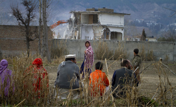 FILE - In this Feb. 26, 2012 file picture, a Pakistan family watches the destruction of Osama bin Laden&#39;s compound in Abbottabad, Pakistan. Bin Laden spent his last weeks in a house divided, amid wives riven by suspicions. On the top floor, sharing his bedroom, was his youngest wife and favorite. The trouble came when his eldest wife showed up and moved into the bedroom on the floor below. &#40;AP Photo&#47;Anjum Naveed, File&#41; <span class=meta>(AP Photo&#47; Anjum Naveed)</span>