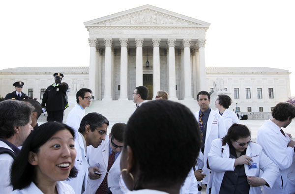 "<div class=""meta ""><span class=""caption-text "">Doctors and medical students supporting the health care reform law signed by President Obama gather in front of the Supreme Court in Washington, Monday, March 26, 2012, as the court begins three days of arguments on health care. (AP Photo/Charles Dharapak)</span></div>"