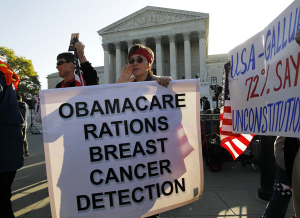 Linda Door of Laguna Beach, Calif. protests against the health care reform law as supporters file past the Supreme Court in Washington, Monday, March 26, 2012, as the court begins three days of arguments on health care. (AP Photo/Charles Dharapak)