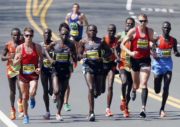 Elite men runners, including Michel Butter, left, of the Netherlands; Levy Matebo, second from left, and Josphat Ndambiri, third from left, of Kenya; Jason Hartmann, second from right, of Boulder, Colo.; and Peter Kamais, right, of Kenya, compete in the Boston Marathon in Wellesley, Mass., Monday, April 16, 2012. (AP Photo/Michael Dwyer)
