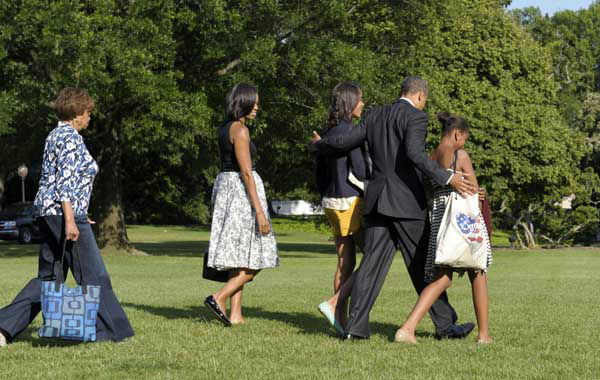"<div class=""meta ""><span class=""caption-text "">President Barack Obama puts his arms around his daughters, Malia, left, and Sasha, right, as he, first lady Michelle Obama, second from left, and mother-in-law Marian Robinson, left, all head to Marine One on the South Lawn of at the White House in Washington, Friday, June 15, 2012. They are heading to Chicago for the weekend. (AP Photo/Susan Walsh) (AP Photo/ Susan Walsh)</span></div>"