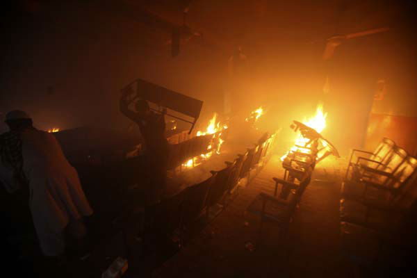 Protesters torch a cinema in Peshawar, Pakistan on Friday, Sept 21, 2012. Tens of thousands protested around the country against an anti-Muslim film after the government encouraged peaceful protests and declared a national holiday ? &#34;Love for the Prophet Day.&#34; Demonstrations turned violent and over a dozen people were killed, including a driver for a Pakistani television station, who died after police opened fire on rioters torching a cinema in the northwest city of Peshawar. &#40;AP Photo&#47;Mohammad Sajjad&#41; <span class=meta>(AP Photo&#47; Mohammad Sajjad)</span>