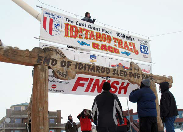 Volunteers hang a banner above the burled arch, which serves as the finish line for the 1,000-mile Iditarod Trail Sled Dog Race in Nome, Alaska, on Monday, March 11, 2013. The race began March 3 in Willow, Alaska, and some race watchers predict a Tuesday finish. &#40;AP Photo&#47;Mark Thiessen&#41; <span class=meta>(AP Photo&#47; Mark Thiessen)</span>